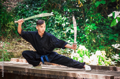 Young man practicing martial arts with a sword Poster