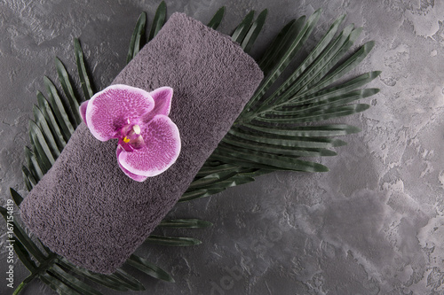 Gray towel and orchid on black marble