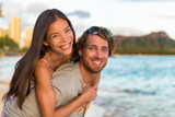 Couple in love on Hawaii travel vacation. Happy Asian woman piggybacking on Caucasian man, multicultural people. Healthy young adults portrait on Waikiki beach, Honolulu, Hawaii. - 167158493