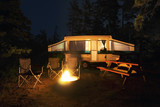 Fototapety Rv trailer, chairs and picnic table around a glowing campfire, wilderness site, night