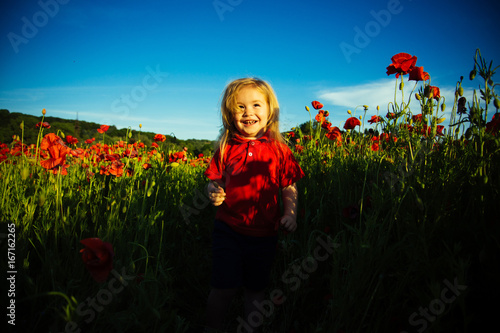 Cute baby, red flower and beautiful field. Happy childhood, sun and flowers, beautiful background. Children's clothing of red color. Summer holidays for children