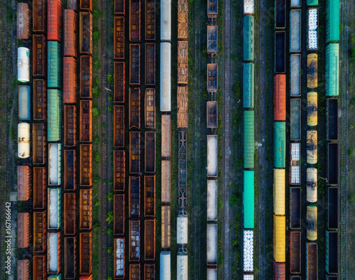 Cargo pociągi z bliska. Widok z lotu ptaka kolorowi pociągi towarowi na staci kolejowej. Wagony z towarami na kolei. Przemysł ciężki. Przemysłowa konceptualna scena z pociągami. Widok z góry od latającego drona