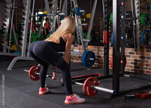 Poster Fitness woman doing a dead lift in the gym