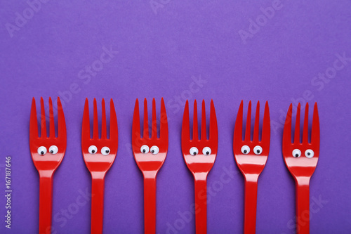 Red plastic forks with googly eyes on a purple background