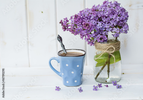 Foto op Canvas Lilac cup of coffee with milk and bouquet of lilac on blue wooden background