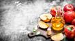 Quadro Apple cider vinegar with fresh apples on cutting Board.