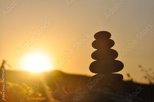 Foto op Plexiglas Zen Silhouette of balanced stone pyramid on mountain. Zen rock, concept of balance and harmony