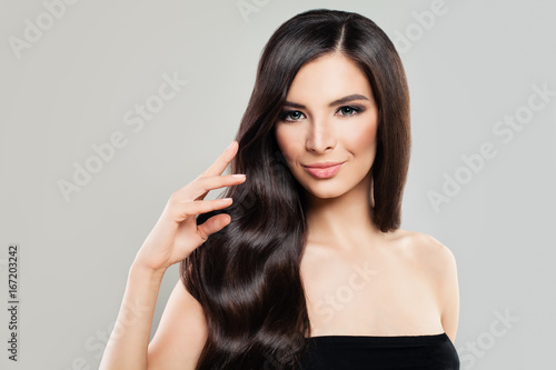 Haircare Concept. Cute Brunette Woman with Natural Perfect Hairstyle and Makeup. Beautiful Model with Long Healthy Hair
