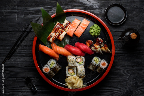 Wall mural Japanese cuisine. Sushi set on a round plate over dark wooden background.