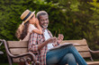 little adorable african american grandchild whispering to her smiling grandfather while sitting on bench in park