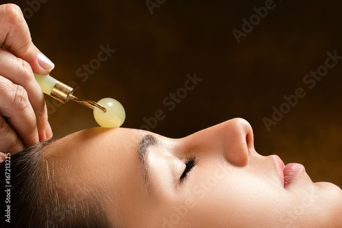 Therapist applying jade roller on female face. - 167213225