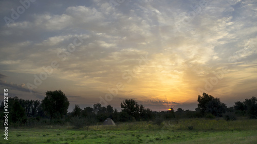 Beautiful sunrise in a field with amazing clouds. Tent. Travels.