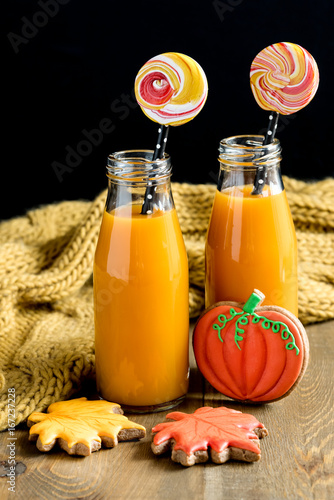 Poster Sap Two bottles of pumpkin juice with black straws Vertical photo Halloween food and sweets concept