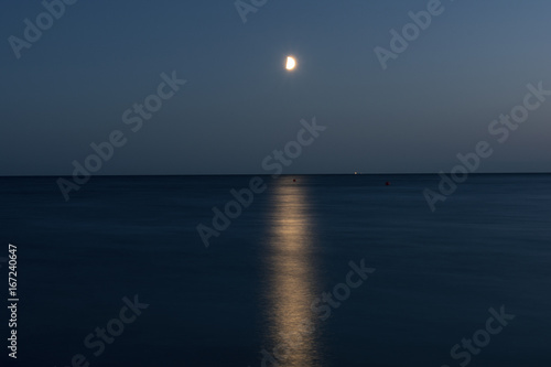 At night a white moon over the sea with a reflection and a path з