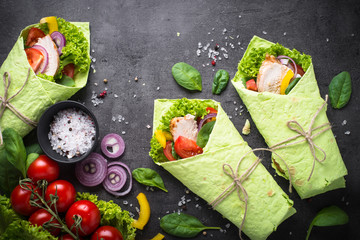 Green spinach tortilla with chicken and vegetables on black slate table. Fast food healthy snack. Top view.