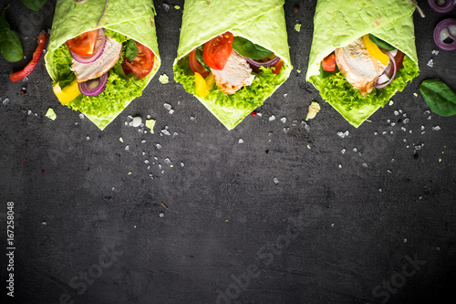 Green spinach tortilla with chicken and vegetables on black slate table. Fast food healthy snack.