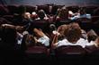 Friends sitting in cinema watch film eating popcorn