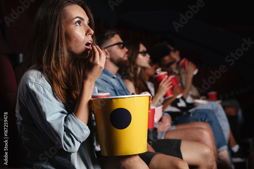 Lady sitting in cinema watch film and eating popcorn.
