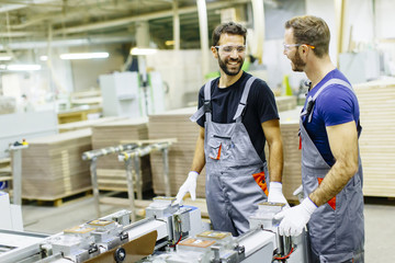 Young workers working in furniture factory