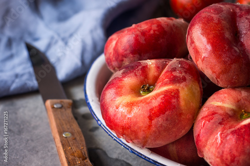 Foto op Canvas UFO Bunch of ripe organic colorful red saturn peaches with water drops on white plate, knife, blue napkin, dark kitchen table, rustic interior