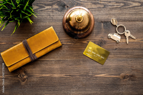 Pay for hotel room. Bank card near hotel service bell on dark wooden table top view copyspace