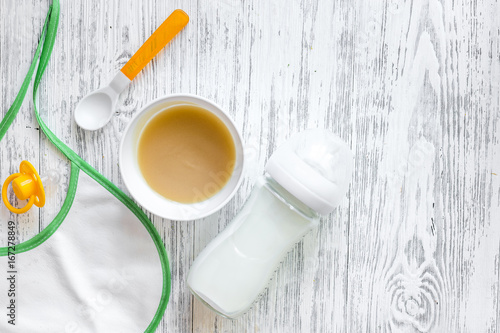 Preparing to feed baby. Puree, spoon, nipple, bottle and bib on light wooden table background top view copyspace