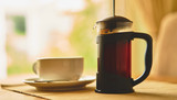 A fresh brew of coffee in a Cafetiere on a breakfast table early in the morning.