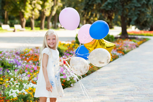 Little beautiful girl playing with balloons Poster