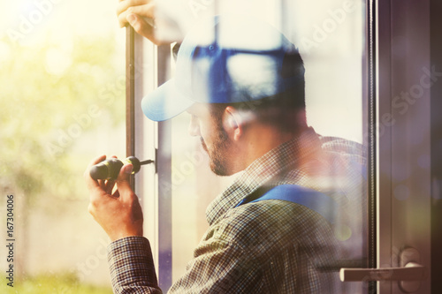 Foto Murales service man installing window with screwdriver
