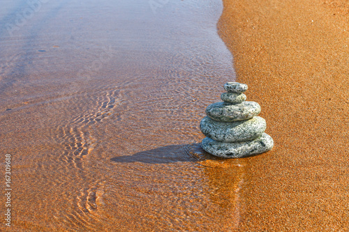 Foto op Canvas Stenen in het Zand Balance stone on sand coast near water