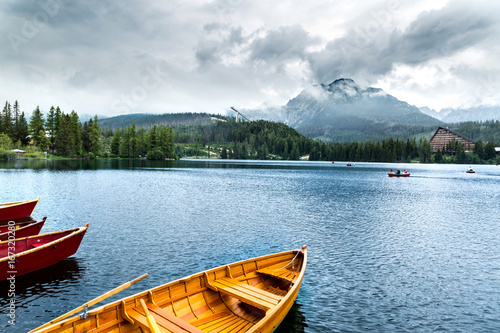 Wooden beautiful boat on a lake surrounded by mountains.