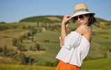 Tuscany tourism - woman in red dress visits Tuscan countryside in Siena province, Italy.