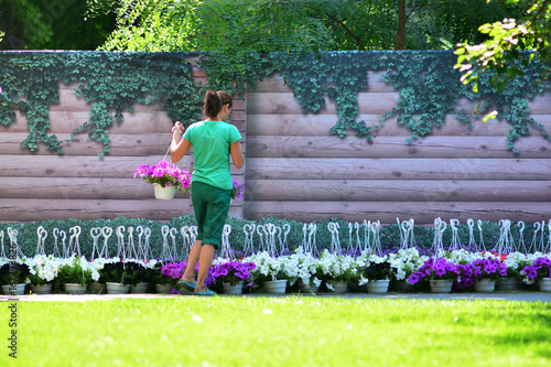 Landscape design. Flower market. The gardener equips the plot in the yard of the house in a sunny summer day.