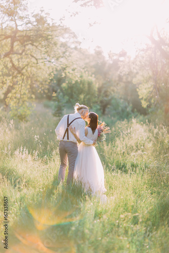 The back view of the kissing newlyweds in the sunny forest. The bride is holding the bouquet.