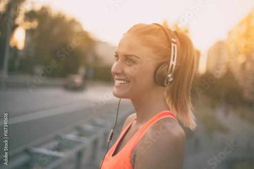 Beautiful sporty woman enjoys listening music.