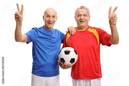 Elderly soccer players making victory signs