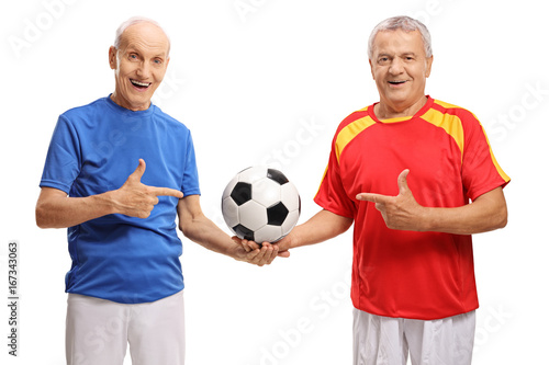 Two elderly soccer players holding a football and pointing