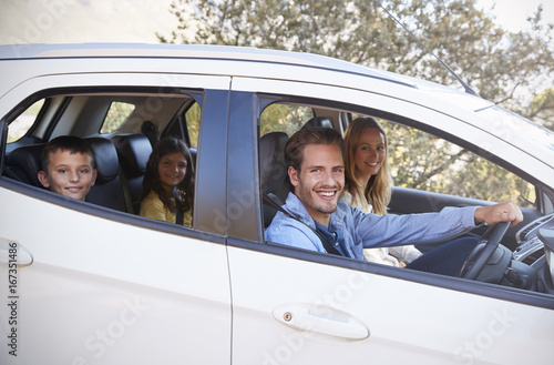 Happy young family driving in their car looking to camera
