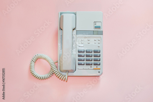 Poster White office telephone on pink background.