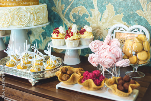 Luxury wedding candy bar with a beautiful white cake decorated with gold ornaments. Concept of chic wedding desserts