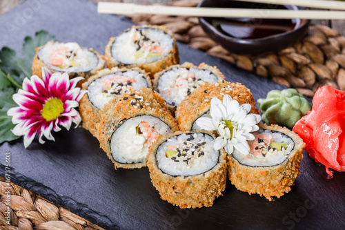 Hot fried Sushi rolls and maki set with Crab Meat, cream cheese, avocado and wasabi on black stone on bamboo mat, selective focus Poster