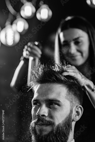 Hair styling man in hairsalon by female hairdresser