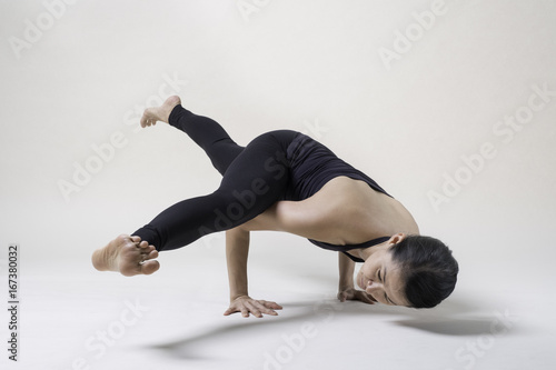 Wall mural Portrait of mid Asian woman is playing yoga in studio in black sport wear.