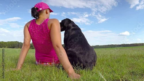 Woman sit with black dog in the grass in the park and relax.