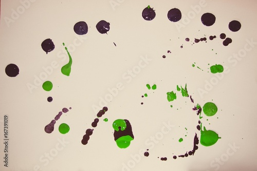 Green and black drops of paint on a white background. - 167391019