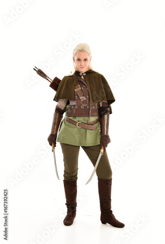 full length portrait of a blonde girl wearing green and brown medieval costume, holding a bow and arrow Poster
