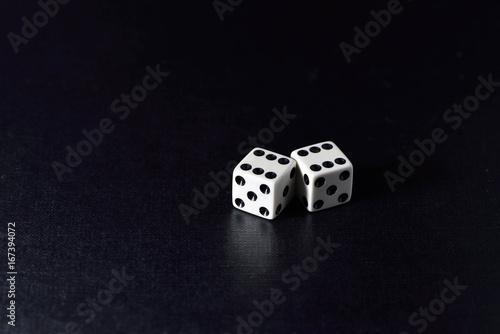 Two white dice  on black плакат