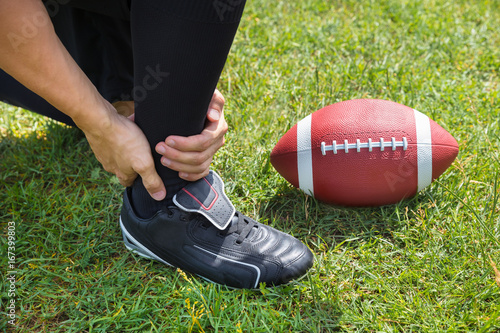 American Football Player With Pain In His Ankle On Field