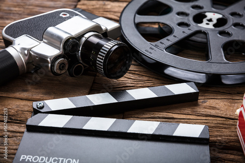 Movie Camera With Film Reel And Clapper Board On Wood