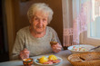 An elderly woman eats sitting at the table. - 167409422